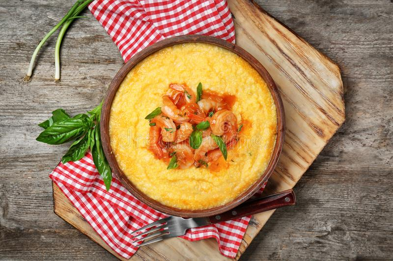 Plate with fresh tasty shrimp and grits on wooden table stock images
