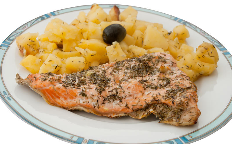 Plate with freshly baked potatoes and salmon fish. Cooked with olive oil, lemon juice, rosemary, thyme, salt, pepper and decorated with an olive royalty free stock images