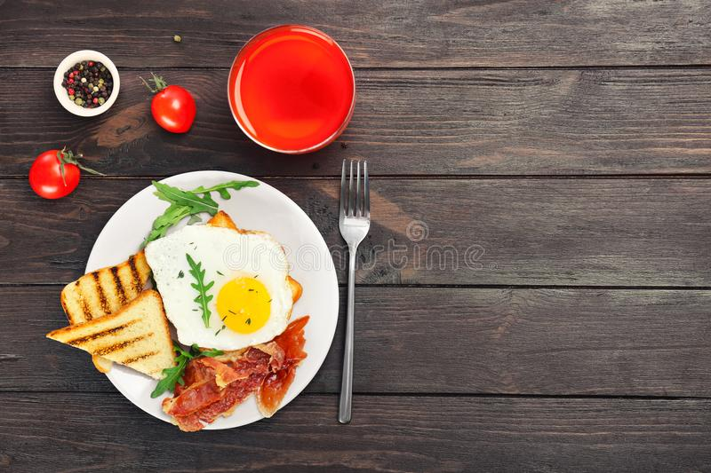 Plate with fried egg, bacon and toasts. On wooden table stock photo