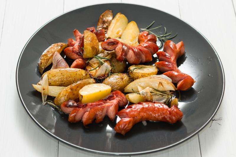 A plate of fried sausage with potatoes, garlic and onions stock photos
