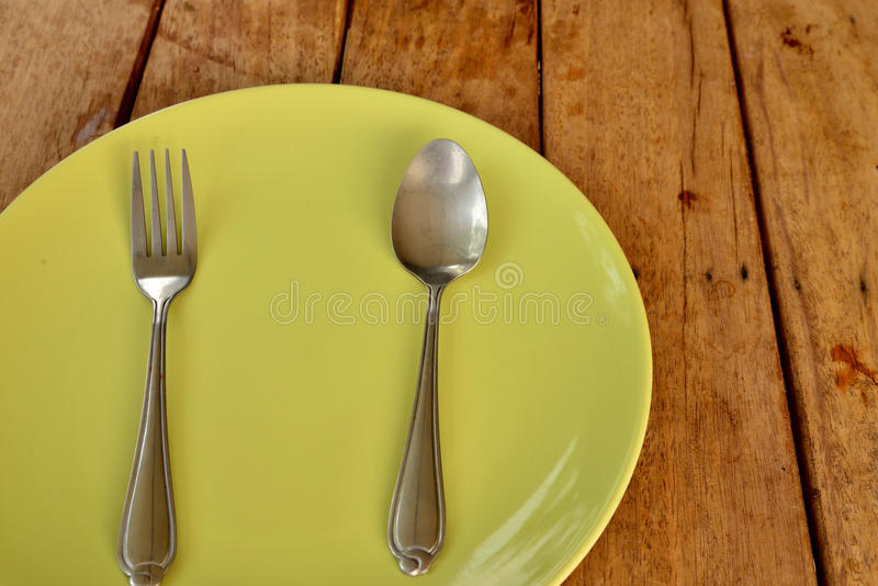 Plate front view on wood background. Empty dinner plate front view on wood background royalty free stock photos