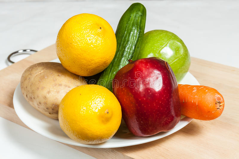 Plate of fruits and vegetables on chopping board. A plate of fruits and vegetables on a cutting board royalty free stock images