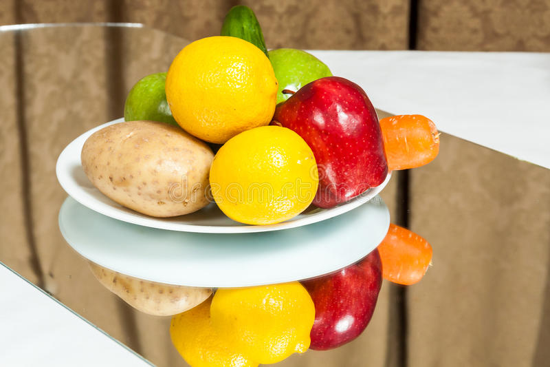 Plate of fruits and vegetables. A plate of fruits and vegetables on a table with mirror reflection royalty free stock image