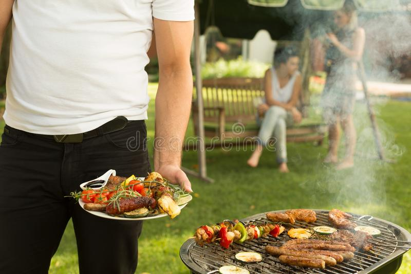Plate full of grilled food. Man holding plate full of grilled food royalty free stock image