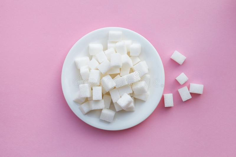 Plate full of sugar cubes on pink background, risk of diabetes, flat layout, top view. White plate full of sugar cubes on pink background, risk of diabetes, flat stock photos