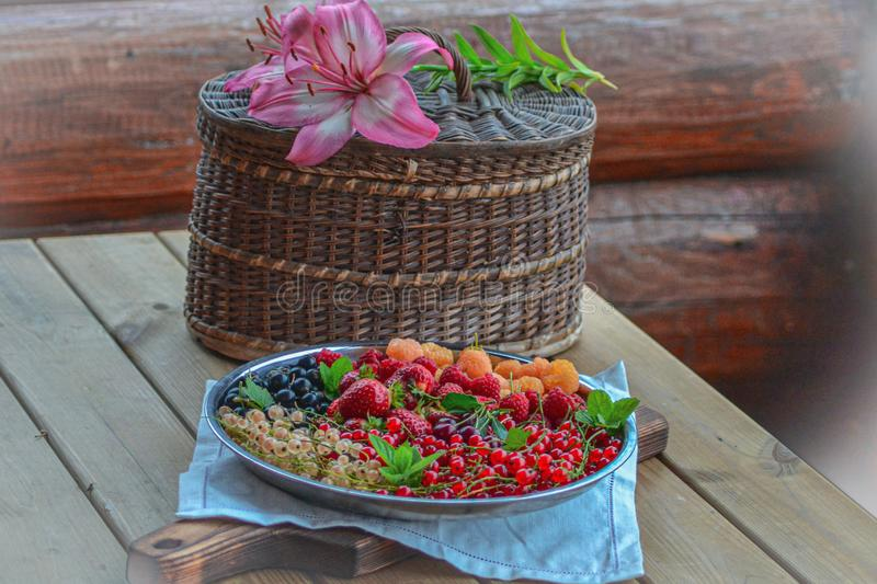Plate with garden berries on the veranda of a wooden house stock photos