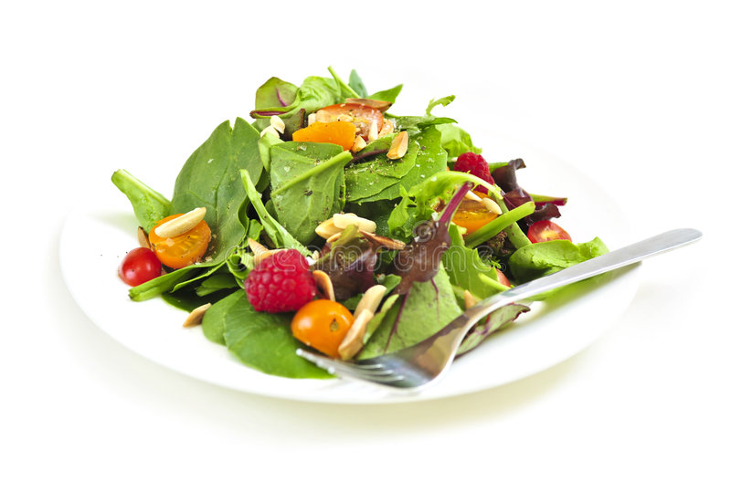 Plate of green salad on white background royalty free stock images