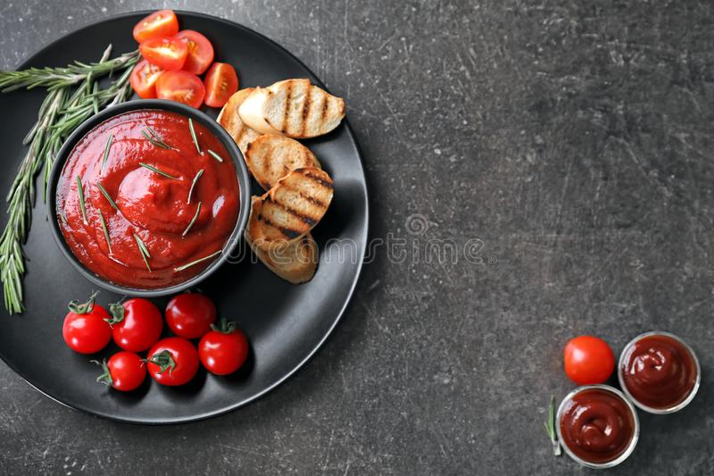 Plate with grilled bread and tasty tomato sauce on table royalty free stock photo