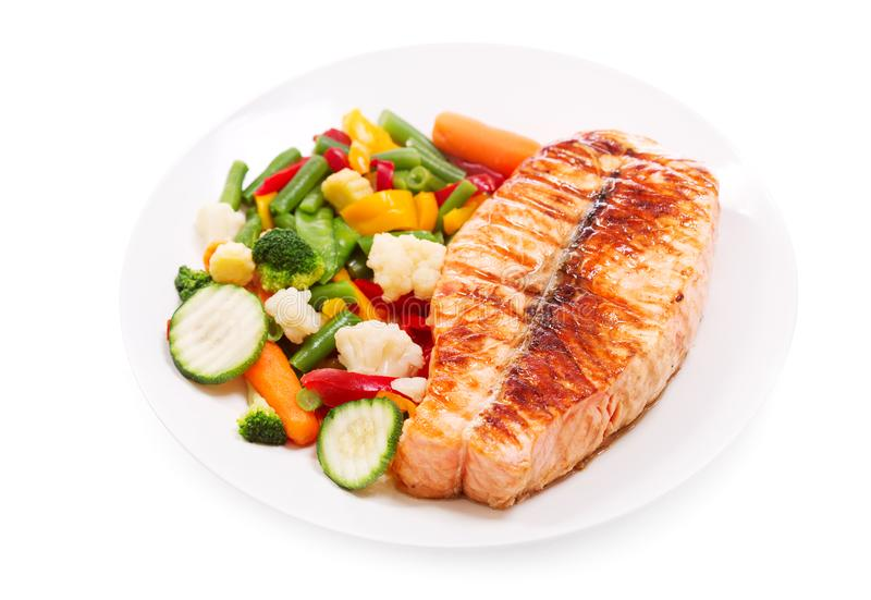 Plate of grilled salmon steak isolated on white background royalty free stock photos