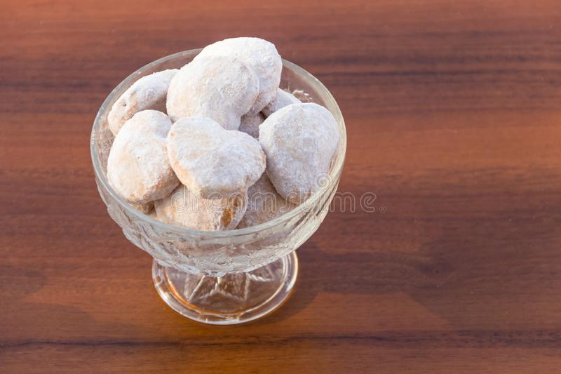 Plate with heart shaped cookies covered with powdered sugar. On wooden table royalty free stock photography