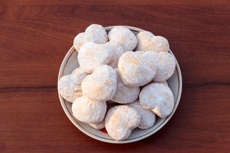 Plate with heart shaped cookies covered with powdered sugar. On wooden table. Top view stock photography