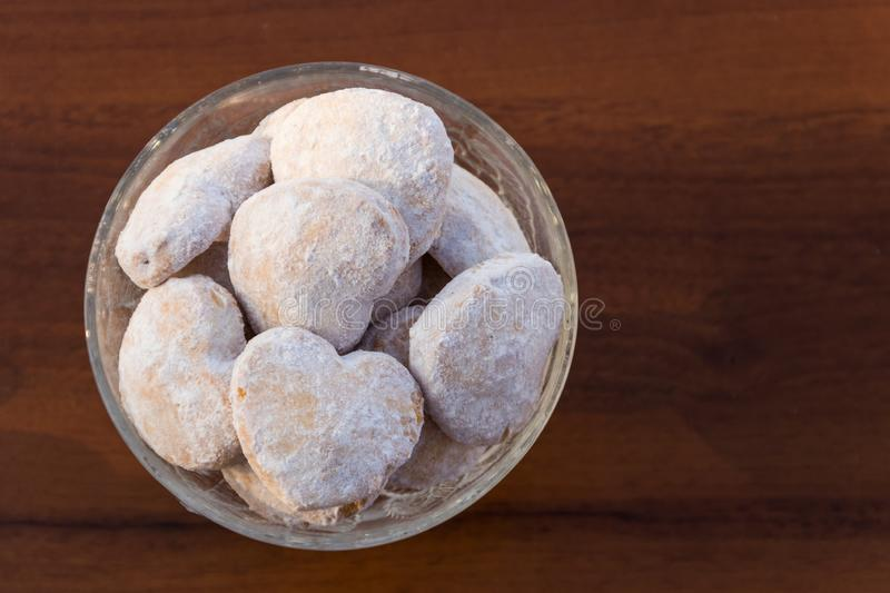 Plate with heart shaped cookies covered with powdered sugar. On wooden table. Top view stock images