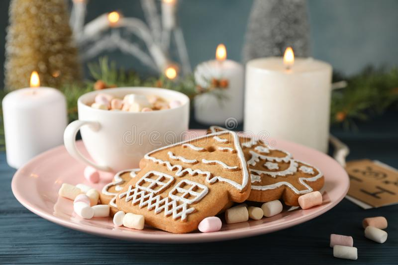 Plate of homemade Christmas cookies, marshmallows on wooden table, against blue background, space for text. Closeup. Plate of homemade Christmas cookies, coffee stock photography