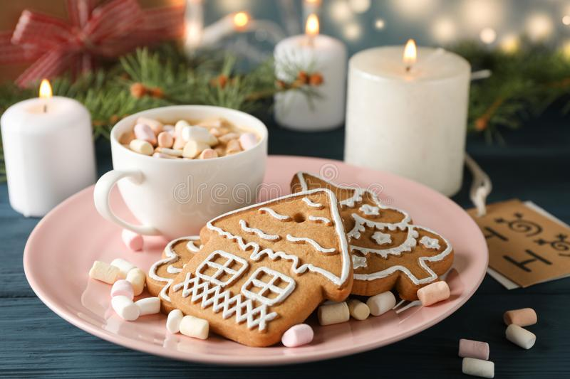Plate of Christmas cookies, coffee, marshmallows on wooden table, against blue background, space for text. Closeup royalty free stock image