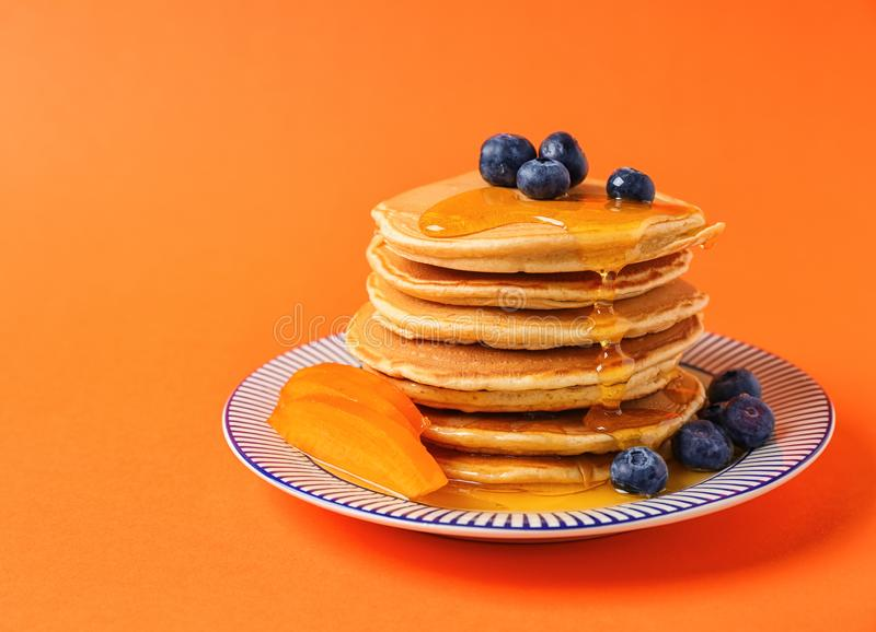 Plate with hot tasty pancakes, sliced persimmon and blueberries on color background royalty free stock photos