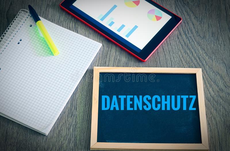 Plate with the inscription in german Datenschutz in English data protection with a tablet and block to signal typical activities. Of data protection officers royalty free stock photography