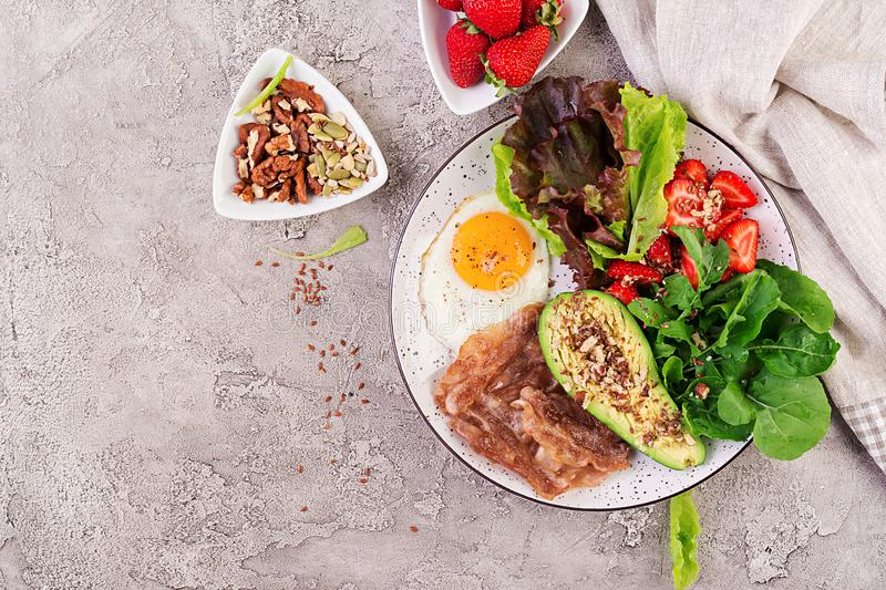 Plate with a keto diet food. Fried egg, bacon, avocado, arugula and strawberries. Keto breakfast. Top view royalty free stock photo