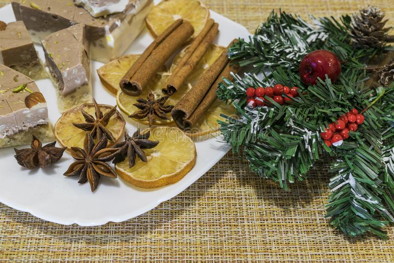 On a plate laid out cakes, cinnamon, star anise, dried lemon. Decorated with artificial pine branch. royalty free stock images