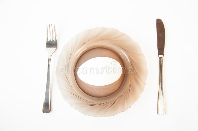 On the plate is a large goose egg. Next to the knife and fork are on the table. On a white background royalty free stock image