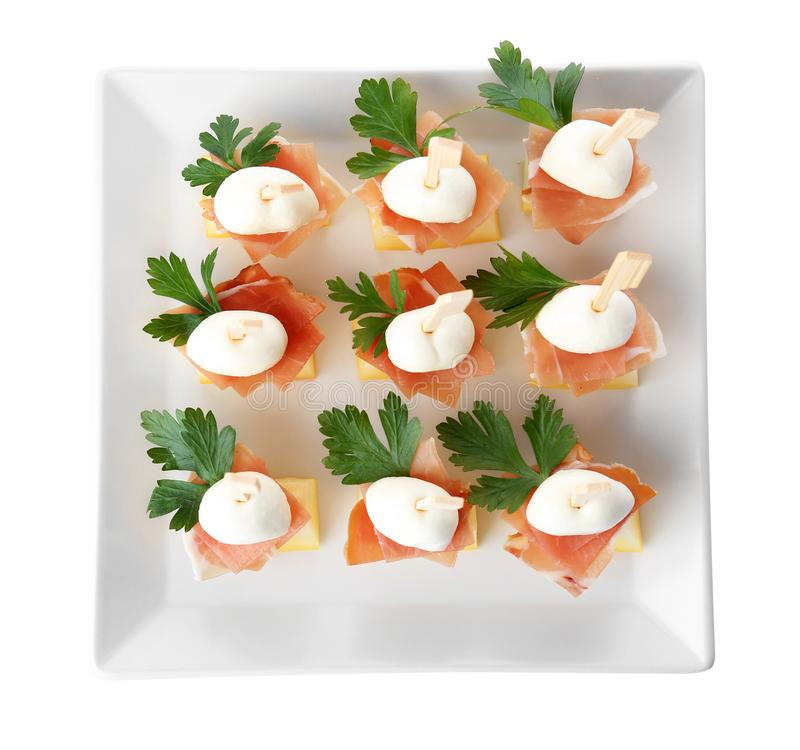 Plate with melon, mozzarella and prosciutto skewers on white background royalty free stock image