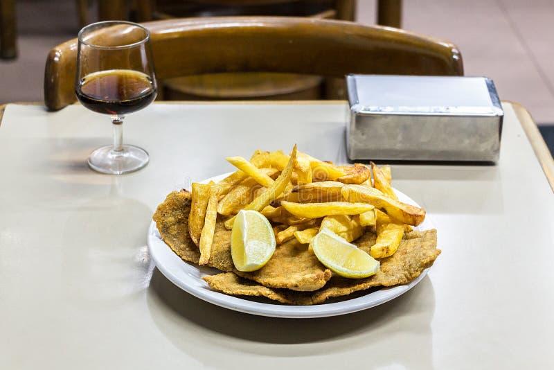 Milanesas con papas fritas & x28;schnitzel made with cow beef and fri. A plate of Milanesas con papas fritas & x28;schnitzel made with cow beef and fries stock photo