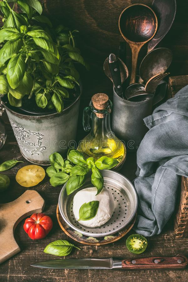 Plate with mozzarella or burrata , oil and basil on rustic kitchen table background with ingredients and cooking stock images