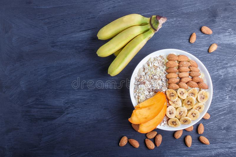 A plate with muesli, almonds, banana, persimmon on a black wooden background with copy space stock photo