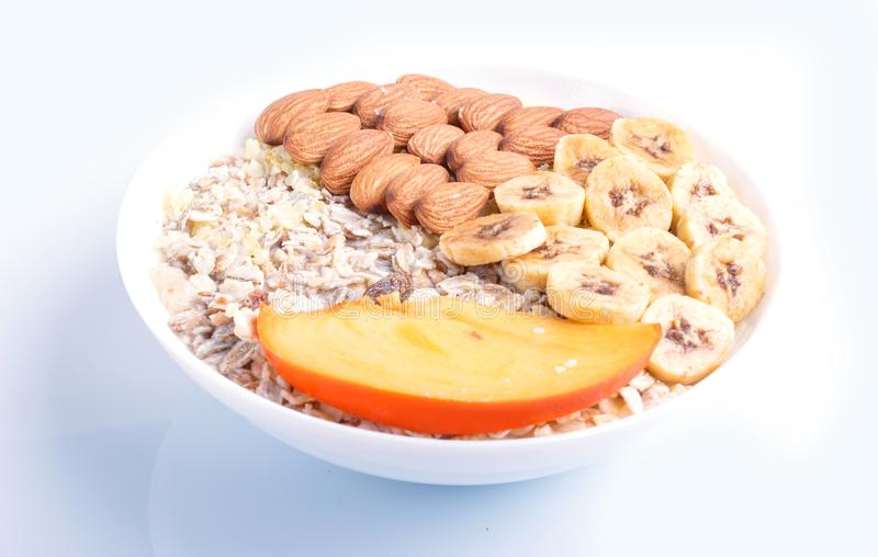 A plate with muesli, almonds, banana, persimmon isolated on white background stock photos
