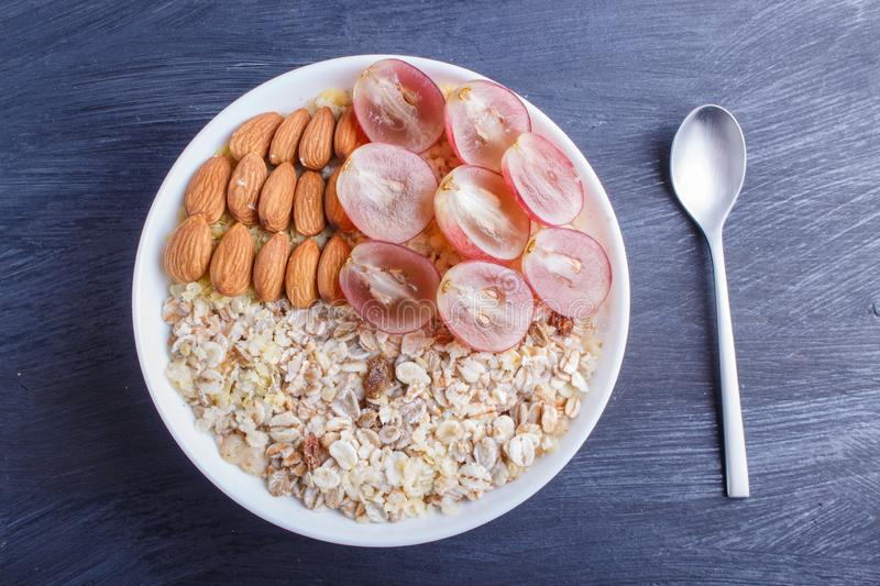 A plate with muesli, almonds, pink grapes on a black wooden background royalty free stock image