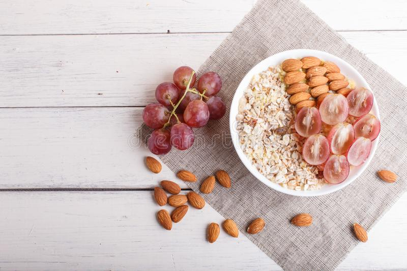 A plate with muesli, almonds, pink grapes on a white wooden background royalty free stock photo