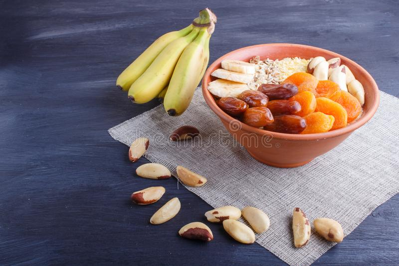A plate with muesli, banana, dried apricots, dates, Brazil nuts on a black wooden background stock images