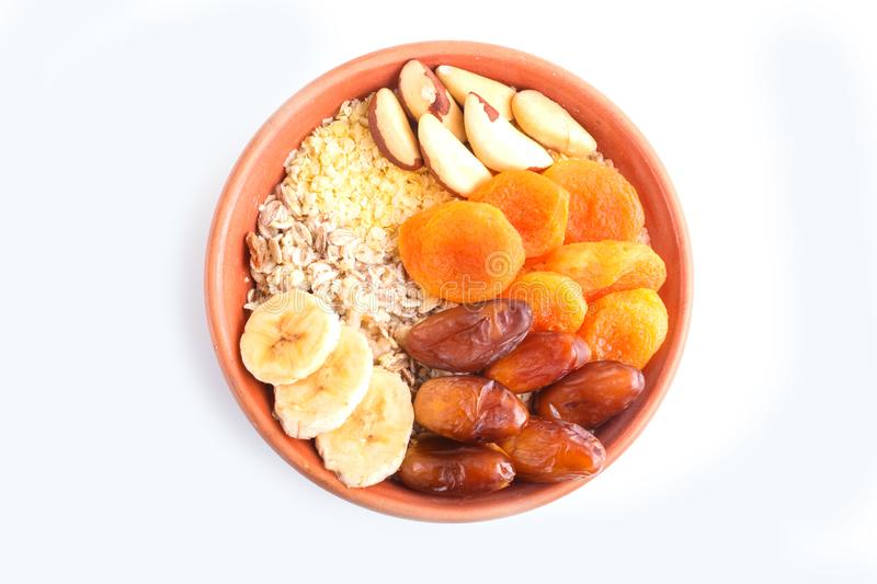 A plate with muesli, banana, dried apricots, dates, Brazil nuts isolated on a white background royalty free stock photography