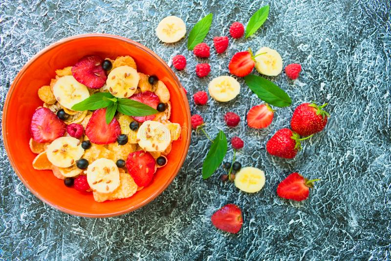 A plate of muesli with berries, banana and flax seeds is decorated with mint leaves. Healthy and healthy breakfast. Top view stock photo