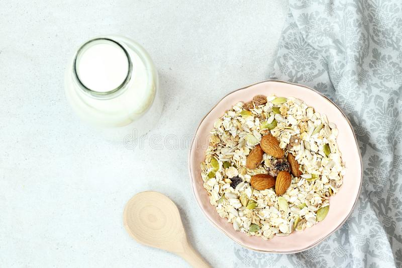 Plate with muesli, bottle of milk and wooden spoon on grey concrete background royalty free stock photography