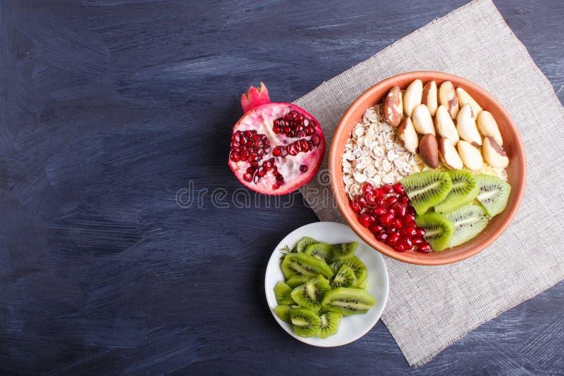 A plate with muesli, kiwi, pomegranate, Brazil nuts on a black wooden background stock photography