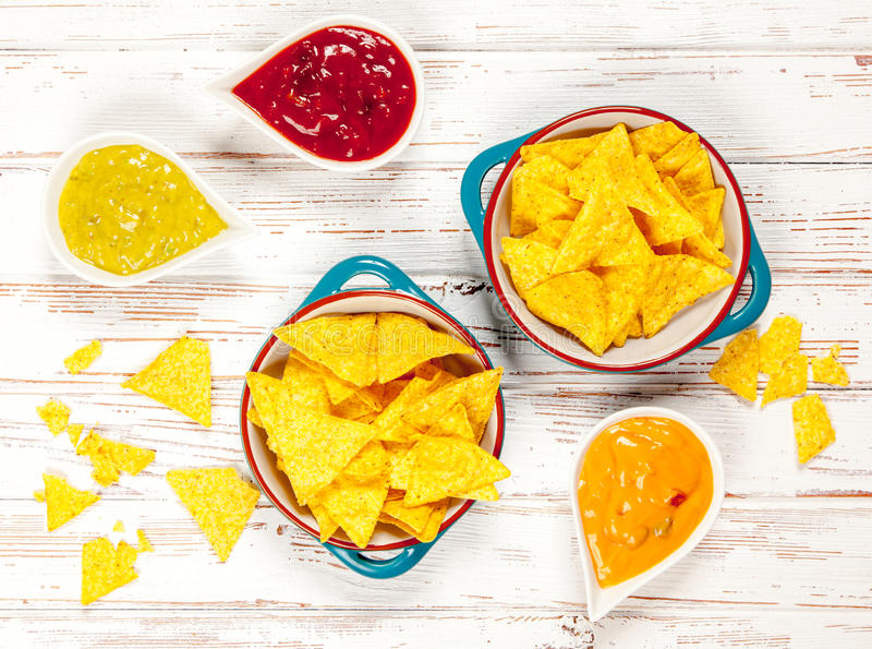 Plate of nachos with different dips. Plate of nachos with salsa, cheese and guacamole dips royalty free stock photos