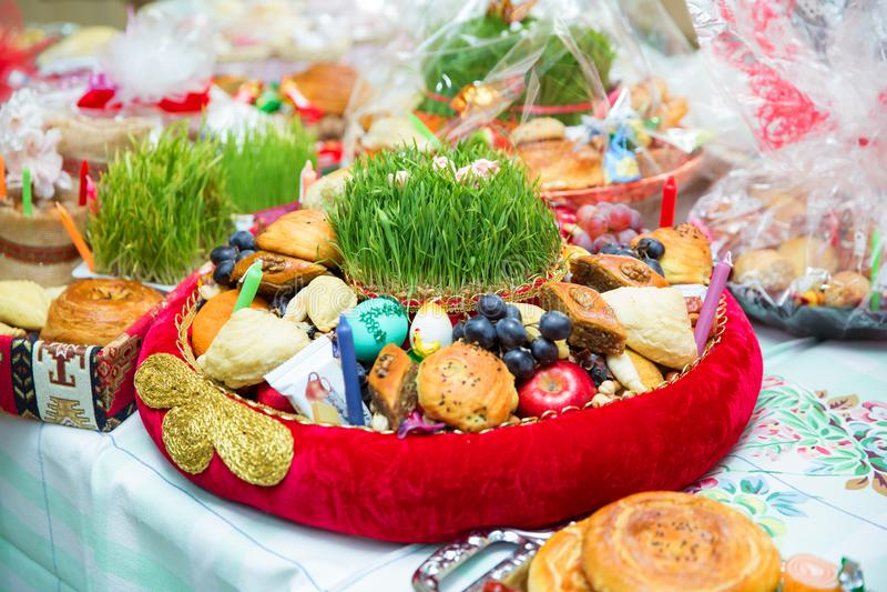 Plate with national sweets pastry for Novruz celebration in Azerbaijan, shekerbura and pakhlava with fresh green wheatgrass semeni stock image