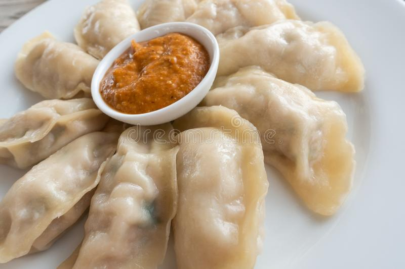 Plate of Nepalese momos. Plate of Nepalese chicken momos and its achar sauce stock photos