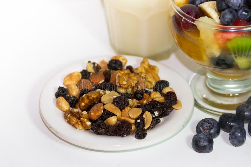 Plate with nuts and cup with fresh fruit salad healthy juices. Healthy breakfasts with fresh ts and dried ts juices, smoothies and t salads stock photography