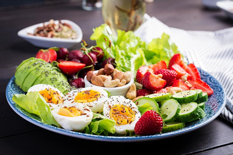 Plate with a paleo diet food. Boiled eggs, avocado, cucumber, nuts, cherry and strawberries. Paleo breakfast royalty free stock images