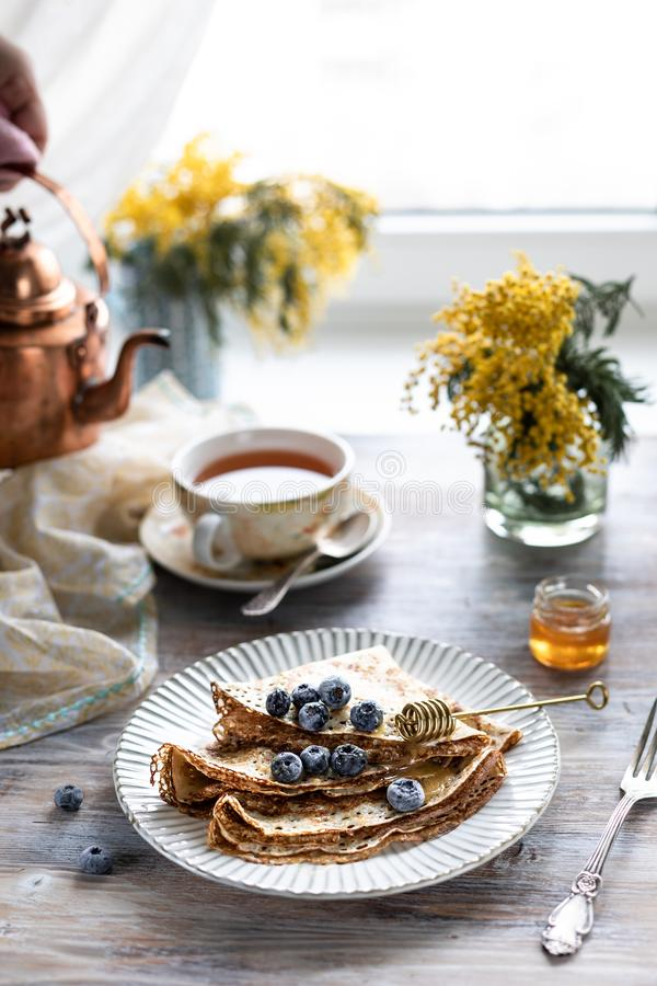 A plate with pancakes with blueberry berries on a wooden table. In the background is a cup of tea and a bouquet of spring flowers royalty free stock photo