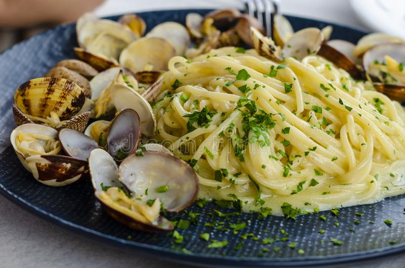 A plate of Pasta with clams and sauce. Traditional italian food. Spaghetti alle vongole or Pasta Posillipo stock photo