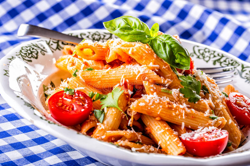 Plate with pasta pene Bolognese sauce cherry tomatoes parsley top and basil leaves on checkered blue tablecloth. stock image