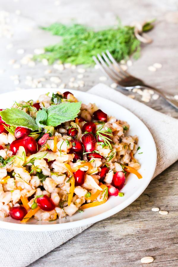 Plate of pearl barley warm salad with carrot, dill and pomegranate seeds in a plate on a wooden table, selective focus. Healthy an. D organic food concept stock photography