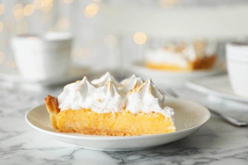 Plate with piece of delicious lemon meringue pie on marble table. Plate with piece of delicious lemon meringue pie on white marble table royalty free stock image