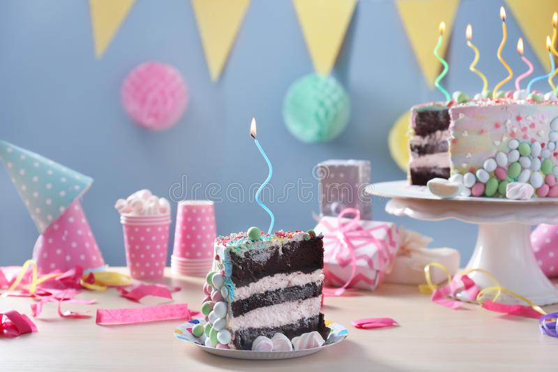 Plate with piece of tasty birthday cake on table royalty free stock photos