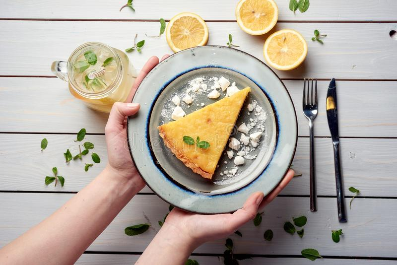 Plate with piece of tasty lemon pie in hands on white wooden table stock image