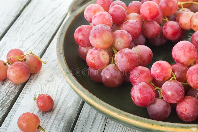 A plate of pink wet grapes royalty free stock photos