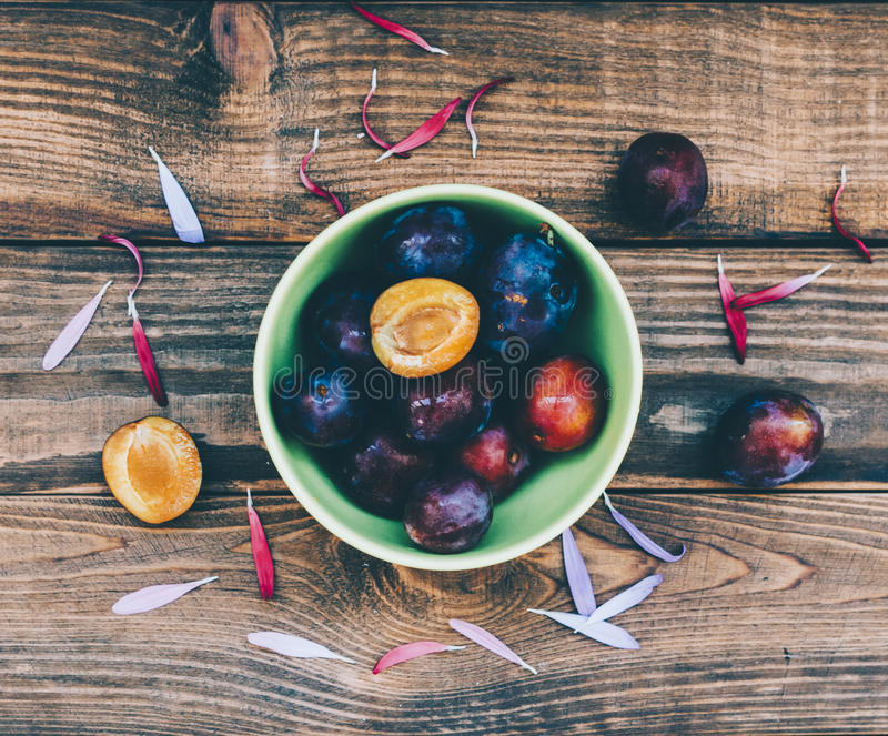Plate With Plums. Green plate with plums over wood board. Top view. Fruits background with space for text. Agriculture, Gardening, Harvest Concept.n stock image