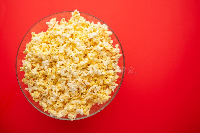 Plate with popcorn on a red background. layout. top view. concept of cinema, viewing, rest stock photos